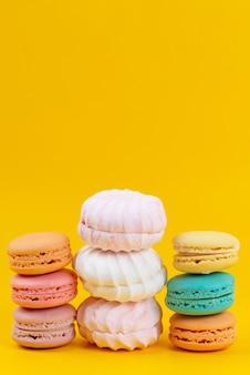 Uma vista frontal de merengues e macarons deliciosos e isolados em amarelo, bolo de biscoito doce confiture