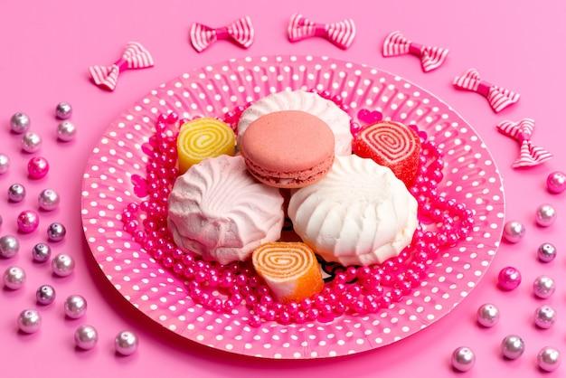 Uma vista frontal de merengues e macarons em rosa, prato e laços em rosa, confeitaria de biscoito de bolo