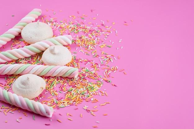 Uma vista frontal de merengues e marshmallow deliciosos com doces coloridos em biscoito de biscoito cor de rosa