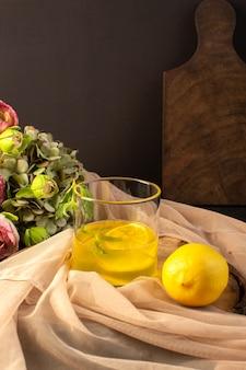 Uma vista frontal de óculos com suco de suco de limão dentro de vidros transparentes ao longo de limão inteiro e flores na mesa de madeira marrom e bebida de limão coquetel de fundo cinza