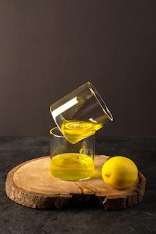 Uma vista frontal de óculos com suco de suco de limão dentro de vidros transparentes ao longo de limão inteiro na mesa de madeira marrom e fundo cinza cocktail bebida de limão