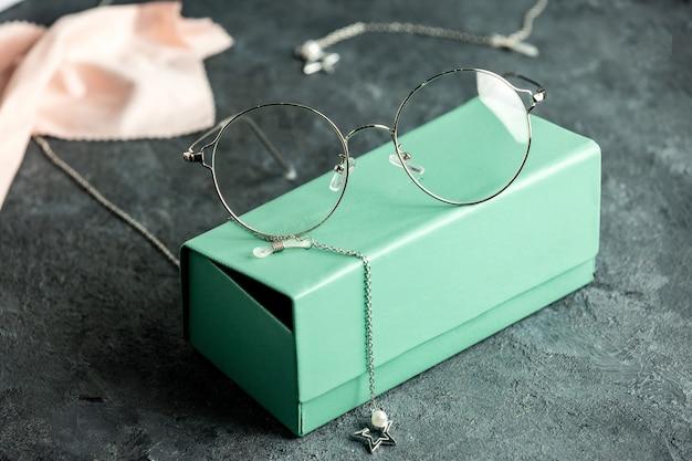 Uma vista frontal de óculos de sol ópticos na caixa de óculos de sol turquesa e mesa cinza com pulseiras de prata