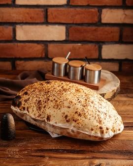 Uma vista frontal de pão assado quente e fresco na mesa de madeira marrom