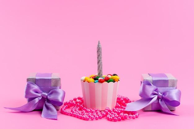 Uma vista frontal de pequenas caixas roxas junto com doces coloridos e velas em um biscoito doce cor de rosa