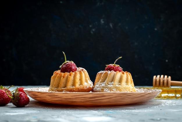 Uma vista frontal de pequenos bolos deliciosos projetados com morangos dentro do prato sobre a mesa de luz
