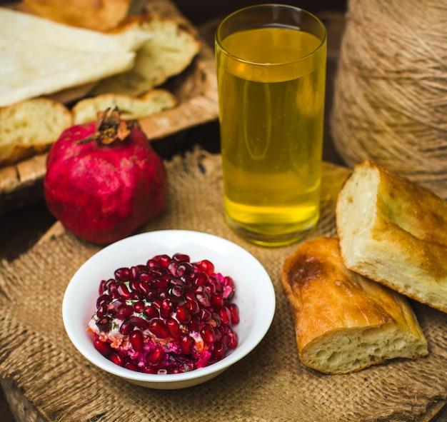 Uma vista frontal de perto romã inteira e descascada junto com suco e pão