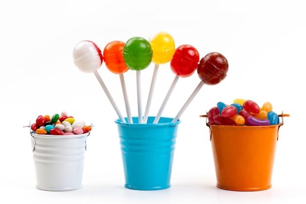 Uma vista frontal de pirulitos coloridos junto com balas multicoloridas dentro de baldes em cor de açúcar branco doce