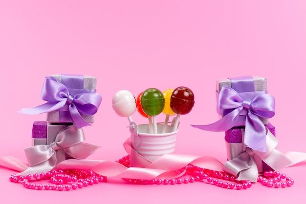 Uma vista frontal de pirulitos e caixas de caixas de presente roxas isoladas em rosa, festa de comemoração de aniversário