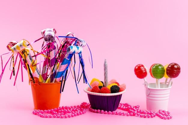 Uma vista frontal de pirulitos e geléias dentro de pequenos baldes junto com apitos de aniversário em açúcar doce rosa