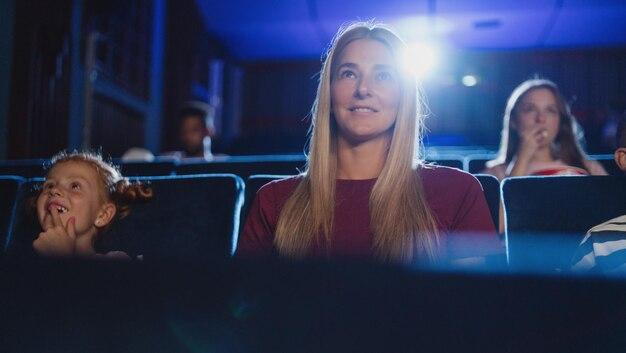 Uma vista frontal de uma jovem alegre no cinema, assistindo ao filme.