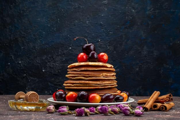 Uma vista frontal deliciosas panquecas com cerejas dentro de um prato branco com flores e canela na mesa escura panqueca de frutas