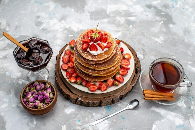 Uma vista frontal deliciosas panquecas redondas com creme e chá de morangos vermelhos e geleia no bolo de mesa de madeira