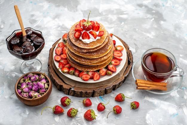 Uma vista frontal deliciosas panquecas redondas com creme e chá de morangos vermelhos no bolo de mesa de madeira