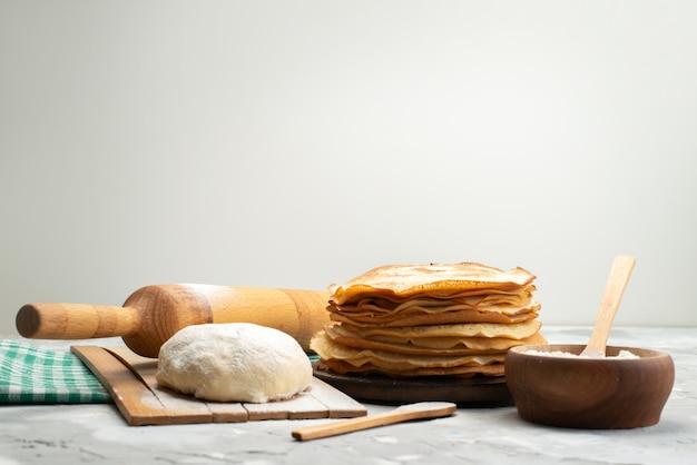 Uma vista frontal deliciosas panquecas redondas com farinha e massa para panquecas cozinhando