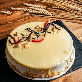 Uma vista frontal delicioso bolo de aniversário decorado gostoso redondo dentro de placa branca aniversário doce biscoito no fundo marrom