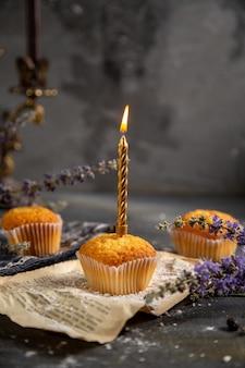 Uma vista frontal deliciosos bolinhos com velas e flores roxas na mesa cinza biscoito chá biscoito doce