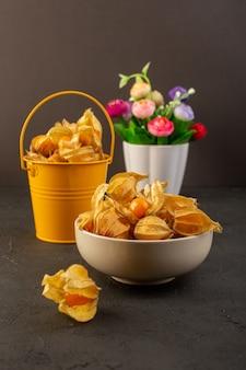 Uma vista frontal descascada frutas laranja redonda dentro da cesta e prato junto com flores em cinza