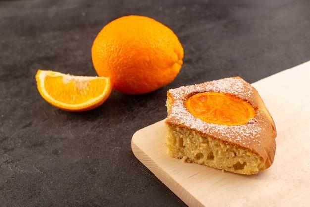 Uma vista frontal do bolo de laranja doce fatias deliciosas de bolo, juntamente com a laranja cortada e inteira sobre o açúcar doce de biscoito de fundo cinza
