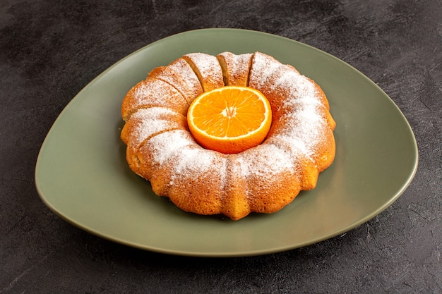 Uma vista frontal doce redondo bolo com varinha de açúcar em pó laranja no meio fatiado doce delicioso prato interior e sobre o fundo cinza biscoito de açúcar