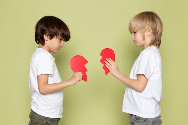 Uma vista frontal dois meninos em camisetas brancas, segurando o coração rasgado vermelho forma no espaço colorido de pedra