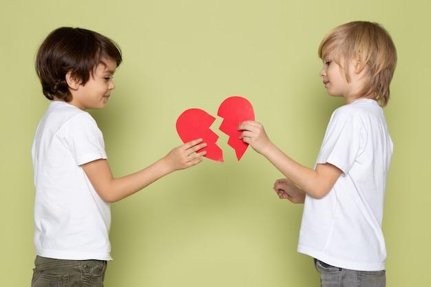Uma vista frontal dois meninos em t-shirt branca segurando coração rasgado forma no espaço colorido de pedra
