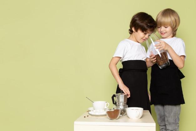 Uma vista frontal dois meninos preparando café beber na mesa de pedra colorida
