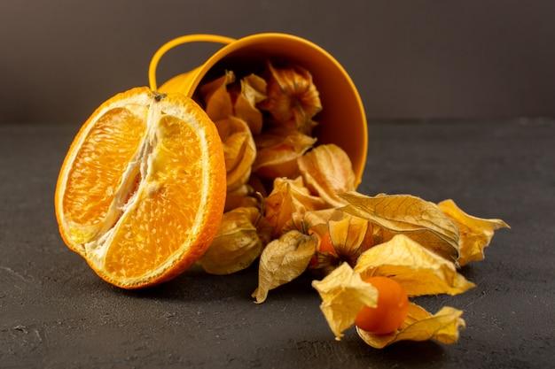 Uma vista frontal em fatias de laranjas, juntamente com frutas redondas alaranjadas descascadas espalhadas no cinza