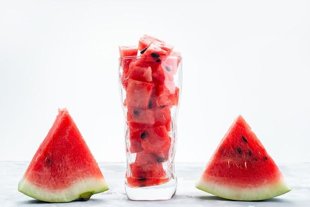 Uma vista frontal em fatias de melancia doce e suave em uma mesa branca