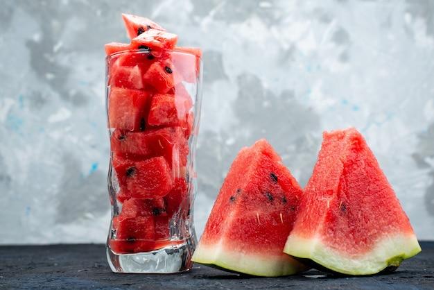 Uma vista frontal em fatias de melancia suave e doce dentro de um copo longo na mesa iluminada