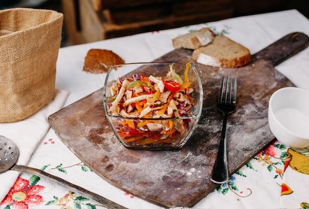 Uma vista frontal em fatias de salada de legumes colorida, enriquecida com vitaminas salgada dentro de uma placa transparente fresca colorida na mesa marrom