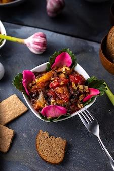 Uma vista frontal fatiada legumes cozidos carne e legumes dentro de chapa branca, juntamente com batatas fritas nacos de pão na mesa cinza refeição saborosa