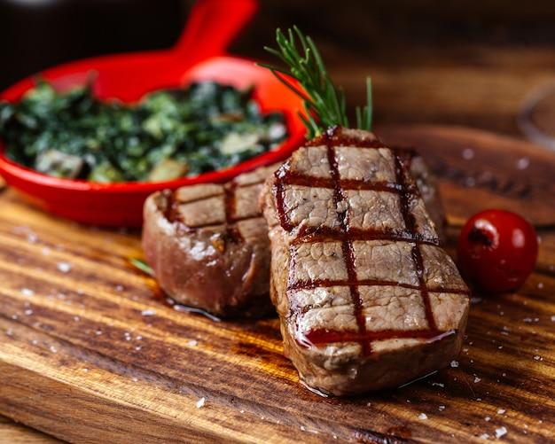 Uma vista frontal fechada de carne frita com molho e verduras junto com um copo de vinho na mesa marrom