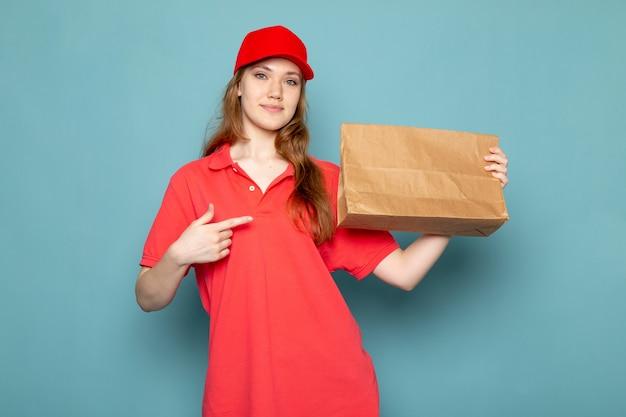Uma vista frontal feminino atraente correio em camisa polo vermelha boné vermelho e calça jeans segurando pacote posando sorrindo sobre o fundo azul