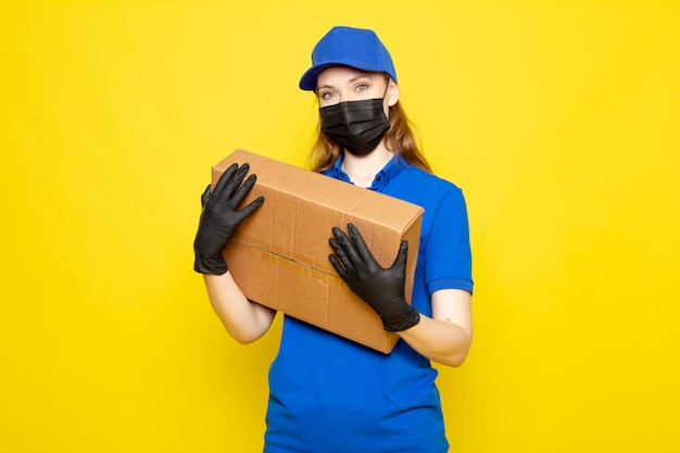 Uma vista frontal feminino atraente correio na camisa polo azul azul boné e calça jeans segurando o pacote em luvas pretas máscara protetora preta posando sobre o fundo amarelo, serviço de alimentação, trabalho