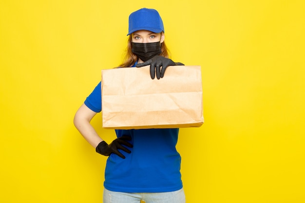 Uma vista frontal feminino atraente correio na camisa polo azul azul boné e calça jeans segurando o pacote em luvas pretas máscara protetora preta sobre o fundo amarelo