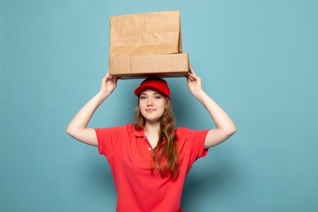 Uma vista frontal feminino atraente courier em camisa polo vermelha boné vermelho segurando pacotes marrons sorrindo posando acima de sua cabeça no trabalho de serviço de alimentação de fundo azul