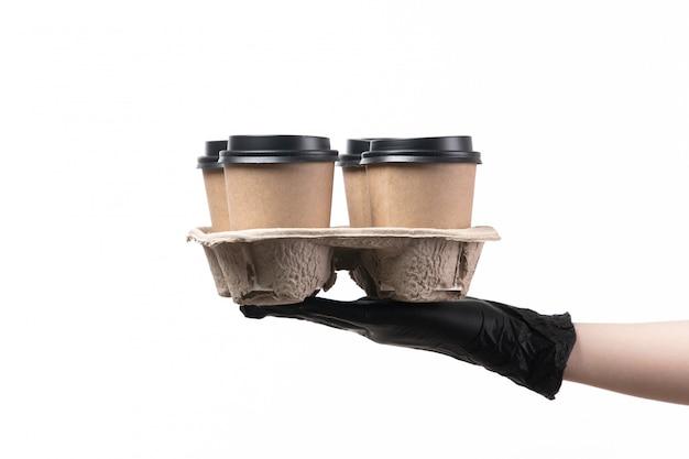 Uma vista frontal feminino mão em luvas pretas segurando copos com café no trabalho branco