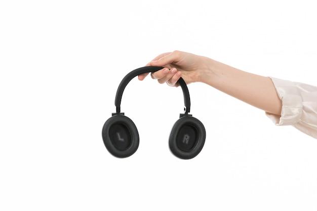 Uma vista frontal feminino mão segurando fones de ouvido pretos no branco