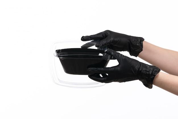 Uma vista frontal feminino mãos em glvoes preto segurando a tigela com comida em branco