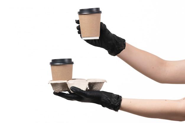 Uma vista frontal feminino mãos em luvas pretas segurando copos de café em branco