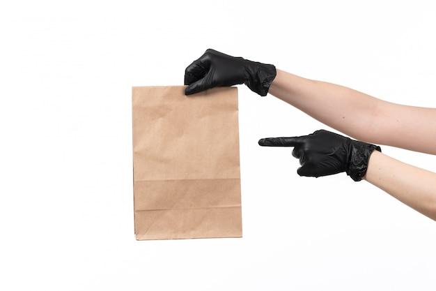 Uma vista frontal feminino mãos em luvas pretas, segurando o pacote de comida de papel em branco