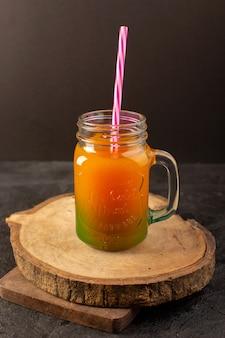 Uma vista frontal frio cocktail colorido dentro de vidro pode com palha colorida isolada na mesa de madeira e escuro