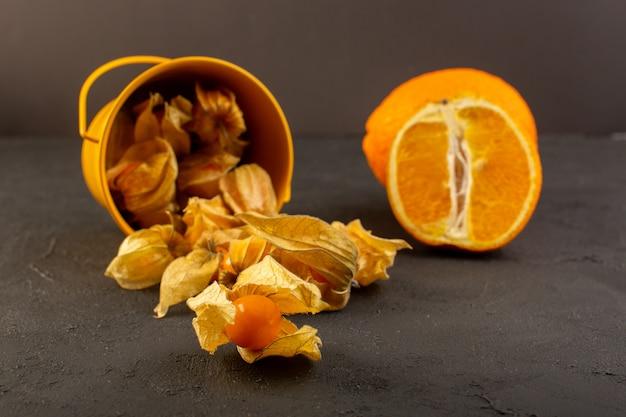 Uma vista frontal frutas alaranjadas com cascas, juntamente com fatias e laranja inteira no escuro
