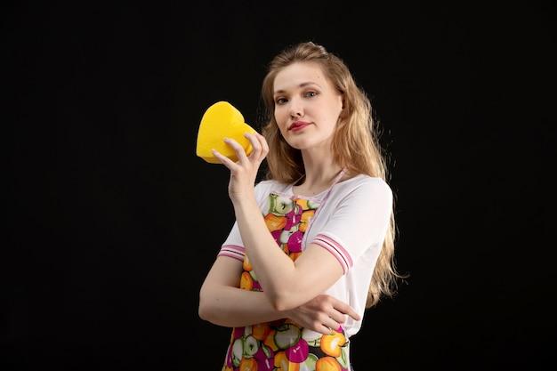 Uma vista frontal garota atraente jovem na capa colorida, sorrindo segurando a forma do coração amarelo sobre o fundo preto amor sorriso positividade