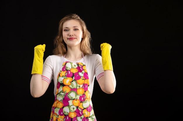 Uma vista frontal garota atraente jovem na capa colorida sorrindo usando luvas amarelas emocionante feliz sobre o fundo preto amor positividade sorriso