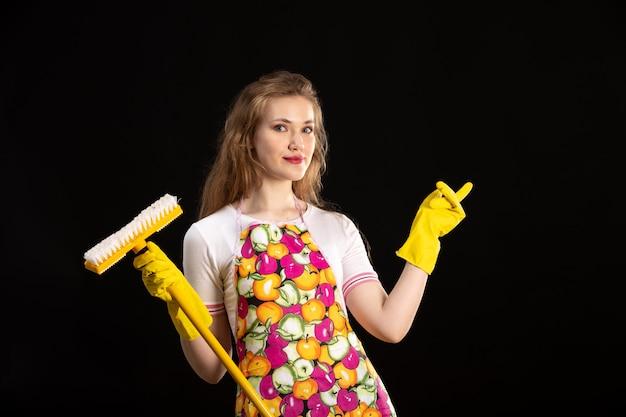 Uma vista frontal garota atraente jovem na capa colorida sorrindo usando luvas amarelas segurando esfregão amarelo sobre o fundo preto positividade sorriso sorriso