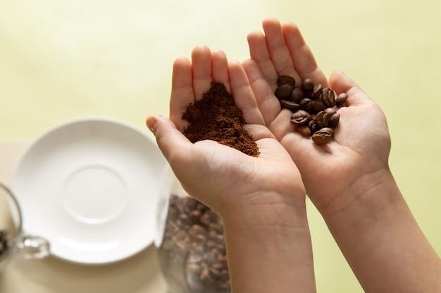 Uma vista frontal garotinho segurando em pó e sementes de café