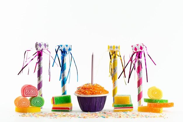 Uma vista frontal geléias e bolo junto com apitos de aniversário em branco, confeitaria doce de cor