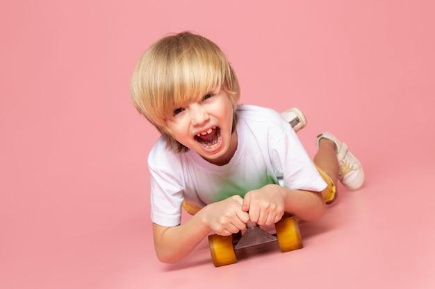 Uma vista frontal gritando menino loiro andando de skate verde no chão rosa