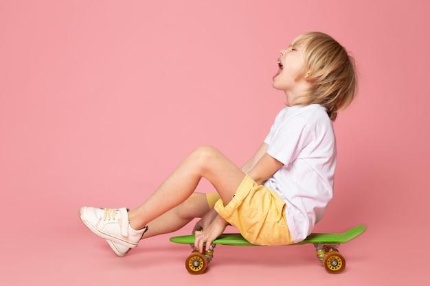 Uma vista frontal gritando menino loiro de cabelos adorável andando de skate verde no espaço rosa